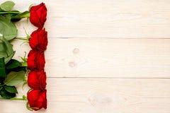 5 czerwonych róż w pionowo rzędzie na białym biurku Fotografia Royalty Free