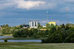 Czluchow, Pomeranian Voivodeship / Poland - June 16, 2019:. Grain silos, view across the lake. A small city in central Europe. Season of the summer stock photo