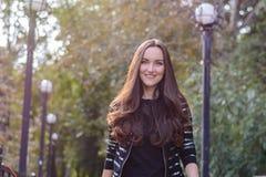 Czołowy portret długowłosa brunetka w jesieni miasta parku Fotografia Stock