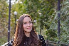 Czołowy portret długowłosa brunetka w jesieni miasta parku Zdjęcia Stock