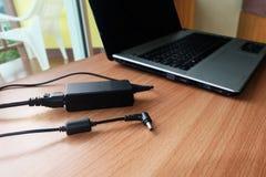 Czopuje wewnątrz adaptator władzy sznura ładowarki laptop Na drewnianym zdjęcia royalty free