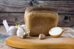 Czosnek, cebula, chleb na stole Zdjęcia Stock