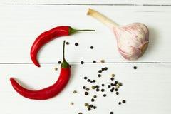 Czosnek, chili, fragrant pieprz na i korzenny, białym drewnianym stole i pieczeniu, zdjęcia stock