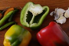 Czosnek, chillies i czerwoni pieprze na drewnianej desce dla przyprawowego jedzenia, obrazy royalty free