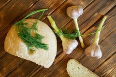Czosnek, koperkowi sprigs i białego round chlebowa babeczka, kłamamy na drewnianym stole robić sosnowe deski ?ycia wci?? lato obraz royalty free