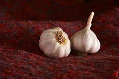 Czosnek na czerwonej tkaninie knedle tła jedzenie mięsa bardzo wiele garlics pokrojony czosnek, czosnku goździkowy, czosnek żarów Zdjęcie Stock