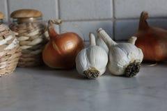Czosnków cloves i cebulkowe żarówki na kuchennym stole z słoma dekorującymi garnkami Obrazy Stock