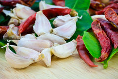 Czosnków cloves, suchy chili, bergamotowi liście pieprzą na drewnianym cutti Zdjęcia Royalty Free