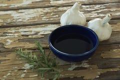 Czosnku żarówki, rozmaryny i olej na drewnianym stole, Fotografia Royalty Free