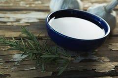 Czosnku żarówki, rozmaryny i olej na drewnianym stole, Obrazy Stock