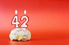 Czterdzieści dwa roku urodzinowego Babeczka z białą płonącą świeczką w postaci liczby 42 zdjęcie royalty free