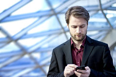 Biznesmen wśrodku biurowy patrzeć na telefon komórkowy Zdjęcie Royalty Free