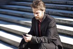 Biznesmen na zewnątrz biurowy patrzeć na telefon komórkowy zdjęcie royalty free