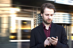 Biznesmen patrzeje na telefon komórkowy na zewnątrz budynek biurowy Fotografia Stock