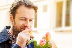 Czterdzieści lat caucasian mężczyzna wącha różowego tulipanu obraz royalty free