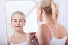 Czterdzieści lat kobieta patrzeje zmarszczenia w lustrze Chirurgii plastycznej i kolagenu zastrzyki makeup Makro- twarz zdjęcia stock