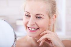 Czterdzieści lat kobieta patrzeje zmarszczenia w lustrze Chirurgii plastycznej i kolagenu zastrzyki makeup Makro- twarz zdjęcie royalty free