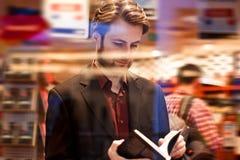 Elegancka mężczyzna pozycja wśrodku bookstore czyta książkę obraz royalty free