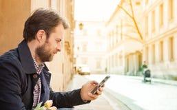 Czterdzieści lat mężczyzna patrzeje telefon komórkowego - miasto Fotografia Royalty Free