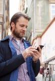 Czterdzieści lat mężczyzna patrzeje telefon komórkowego - miasto zdjęcie royalty free