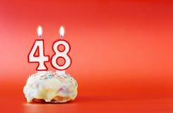 Czterdzieści osiem rok urodzinowych Babeczka z białą płonącą świeczką w postaci liczby 48 obraz royalty free