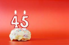 Czterdzieści pięć rok urodzinowych Babeczka z białą płonącą świeczką w postaci liczby 45 fotografia stock