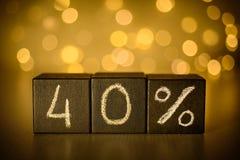 40% czterdzieści procentu znaka kreda pisać na czarnych sześcianach na zamazanym bokeh tle zdjęcie stock