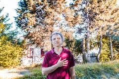 Czterdzieści rok dorosłego trzyma jego rękę na sercu zdjęcia royalty free