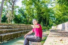 Czterdzieści rok dorosłego wskazuje na średniowiecznych krokach wzdłuż wody zdjęcia stock