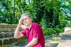 Czterdzieści rok dorosłej mienie głowy na średniowiecznych krokach wzdłuż wody zdjęcia stock
