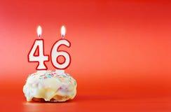 Czterdzieści sześć rok urodzinowych Babeczka z białą płonącą świeczką w postaci liczby 46 obrazy stock
