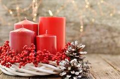 Cztery świeczki w białym wianku z czerwonymi jagodami na drewnianym nieociosanym tle z światłami nastanie kalendarz dla bożych na zdjęcia royalty free