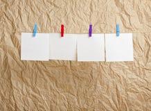 Cztery biel pustej notatki wiesza na clothesline na rzemiośle tapetują Obrazy Stock
