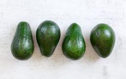 Cztery całej avocado bonkrety na białej desce strzelającej z góry obrazy stock