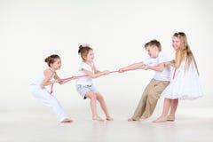 Cztery chłopiec i dziewczyny w biel ubraniach rysują nad arkaną Zdjęcia Royalty Free