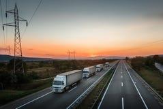 Cztery ciężarówek ciężarówek Biały konwój na autostradzie zdjęcia royalty free