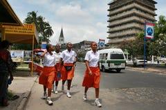 Cztery czarnych afrykanów dziewczyna w pomarańcz spódnicach i białych bluzkach Zdjęcie Royalty Free