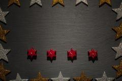 Cztery czerwieni gwiazdowej świeczki na łupku z gwiazdy ramą Zdjęcia Royalty Free