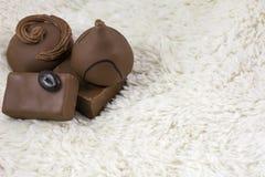 Cztery dojnego czekoladowego cukierku są na białym futerku Obraz Royalty Free