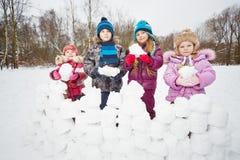 Cztery dzieci stojak za ścianą robić od śnieżnych cegieł obrazy stock
