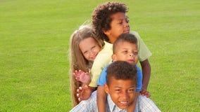 Cztery dziecka bawić się na trawie zbiory wideo