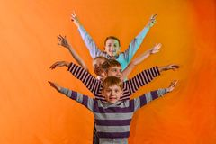 Cztery dziecka stoją z rzędu i podnoszą ich ręki strony na wieku żółty tło młodzi ones spojrzenie za dla zdjęcie royalty free