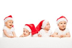 Cztery dziecka stoją z rzędu odzież czerwonych Bożenarodzeniowych kapelusze obraz stock