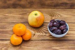 Cztery jaskrawej pomarańczowej dojrzałej mandarynki, jabłko i filiżanka z datami, zdjęcia royalty free