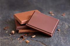 Cztery kwadrata zmrok i dojna czekolada odizolowywający na popielatym łupku Mali kawałki czekolada 50mm plam tła wpływu pożarów n zdjęcie royalty free