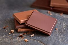 Cztery kwadrata zmrok i dojnej czekolada z małymi czekoladowymi kawałkami na popielatym łupku Zamazana czekolada w tle obraz stock