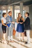 Cztery ludzie biznesu opowiada w biuro lobby Zdjęcie Stock