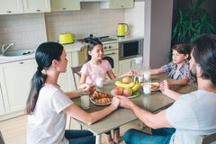 Cztery ludzie rodzina siedzą przy stołem i chwytami wpólnie each inny ręki Utrzymują oczy zamykają fotografia stock