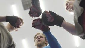 Cztery ludzie stoi w okręgu nad kamera w gym Firma męskie i żeńskie atlety stawia ich pięści wewnątrz zbiory wideo