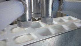 Cztery napełniacza nalewają ciężką śmietankę w białych zbiorniki zbiory wideo